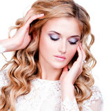 Woman with long blond curly hair looking down Royalty Free Stock Photography