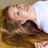 Woman with long blond hair. A picture of a woman with long blond hair, lying down on the floor and looking into the camera to her side stock photo