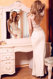 Woman with long blond hair in elegant beige dress Royalty Free Stock Image