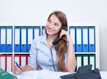 Woman with long blond hair at office speaking with a client at phone Royalty Free Stock Photography