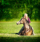 Woman with long blond hair sitting on lying horse and smiling royalty free stock photography