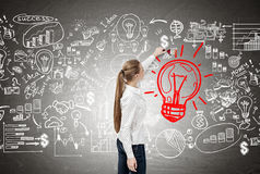 Woman with long blond ponytail drawing a red light bulb Royalty Free Stock Image