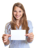Woman with long blonde hair has a blank gift card for christmas in her hands Royalty Free Stock Photos