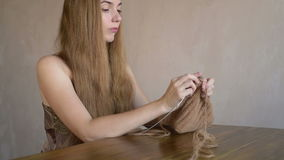 Woman with long blonde hair knitting stock footage