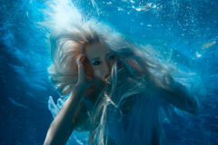 Woman with long blonde hair underwater. Stock Images