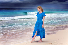The woman in a long blue dress goes on the sea coast Stock Photos