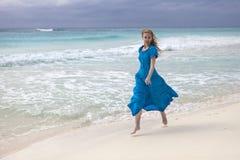 Woman in a long blue dress goes on the sea coast Cayo Largo island, Cuba.  royalty free stock photo