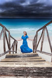 The woman in a long blue dress goes on the stormy sea Royalty Free Stock Photography