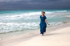 Woman in a long blue dress goes on the stormy sea coast. The woman in a long blue dress goes on the stormy sea coast royalty free stock photography