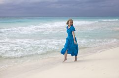 Woman in a long blue dress goes on the stormy sea coast. The woman in a long blue dress goes on the stormy sea coast stock photos