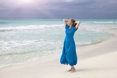Woman in a long blue dress goes on the stormy sea coast. The woman in a long blue dress goes on the stormy sea coast royalty free stock images