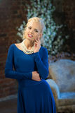 Woman in long blue dress. Luxury interior Royalty Free Stock Images