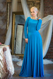 Woman in long blue dress. Luxury interior Royalty Free Stock Image