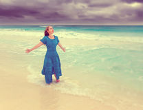 The woman in a long blue dress in a surf of stormy sea,with retro effect Royalty Free Stock Photos