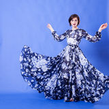 Woman with long blue flying dress in studio photo. Elegance and beauty Royalty Free Stock Photo