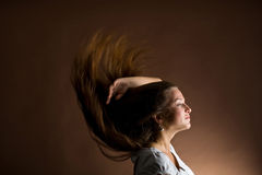 Woman with long brown hair. Fashion portrait of a young woman with hair lightly fluttering in the wind on a dark background Royalty Free Stock Image