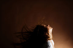 Woman with long brown hair. Fashion portrait of a young woman with hair lightly fluttering in the wind on a dark background Stock Photo