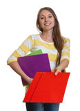Woman with long brown hair giving red file. Attractive young woman with long brown hair and colorful paperwork in her hands giving an red file on an isolated Royalty Free Stock Photos