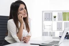 Woman with long brown hair is on the phone in a white office Stock Photo