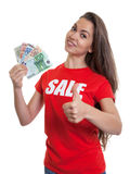 Woman with long brown hair in sale shirt saving money Royalty Free Stock Photography