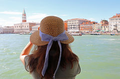 Woman with long brown hair and a straw hat and the great bell to. Young woman with long brown hair and a large straw hat and the great bell tower in Venice in Stock Photo