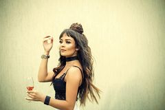 Woman with long brunette hair in black lace bustier. Girl holding glass of wine on beige wall. Cocktail party or holiday celebration. Drinking alcohol concept stock photo
