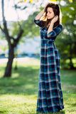 A woman in long checkered dress. Romantic girl in the spring park. A woman walks in the park in a casual dress. Green field on vac Royalty Free Stock Photos