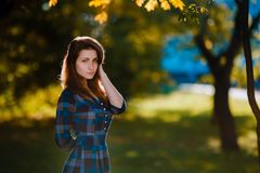 A woman in long checkered dress. Romantic girl in the spring park. A woman walks in the park in a casual dress. Green field on vac Stock Images