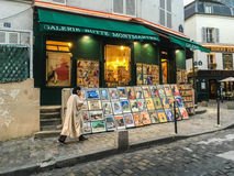 Woman in long coat walks past print shop on Montmartre, Paris. France Stock Image