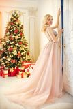 Woman in a long cream-coloured dress, standing near the Christmas tree and the door. Luxurious blonde in evening dress celebrate stock photos