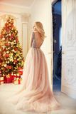 Woman in a long cream-coloured dress, standing near the Christmas tree and the door. Luxurious blonde in evening dress celebrate royalty free stock photos