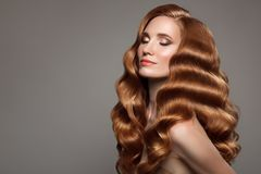 Portrait of woman with long curly beautiful ginger hair. Stock Image