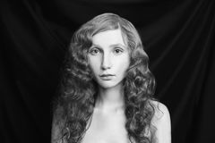 Art black and white photography. Unusual appearance. Woman with long curly flowing hair on a black background. Black and white art monochrome photography Stock Photos