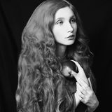 Art black and white photography. Unusual appearance. Woman with long curly flowing hair on a black background. Natural beauty. The girl from the era of Stock Photography