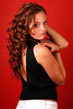 Woman with long curly hair. Young attractive woman with long curly hair on a red background stock photography