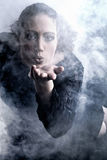 Woman with long curly hair blowing smoke Stock Photos