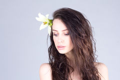 Woman with long curly hair and lily in hair looking down. SPA and beauty. Royalty Free Stock Photo