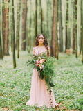 The woman with long curly hair in the long light pink dress is holding the huge bouquet of red, white flowers and green Royalty Free Stock Images
