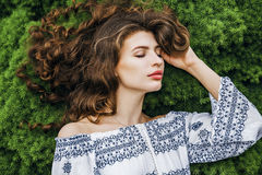 Woman with long curly hair lying on spring grass Royalty Free Stock Photography