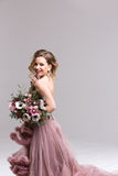 Woman with long curly hair in a pink dress and Wedding Flowers. royalty free stock photography