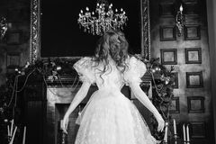 Art black and white photography. Unusual appearance. Woman with long curly hair in a white vintage wedding dress with white pearl earrings on her ears Stock Image