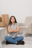 Woman with long dark hair relaxing in new apartment after relocation. Stock Image