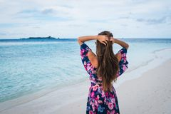 Woman in long dress on beach with pure water of ocean in Maldives. Woman in long dress on beach with pure blue water of ocean in Maldives Royalty Free Stock Image