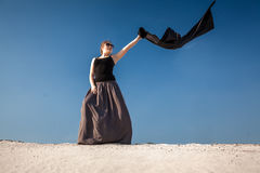 Woman in long dress with black cloth standing on sand dune Royalty Free Stock Photo