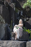 Woman in a long dress on black stones. Polynesia. Royalty Free Stock Image