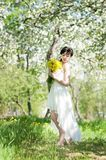 Woman in long dress in blossom apple park. Spring Royalty Free Stock Image