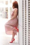 Woman in long dress on city street Stock Photo
