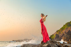Woman in long dress in front of sea Stock Image