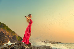 Woman in long dress in front of sea stock photo