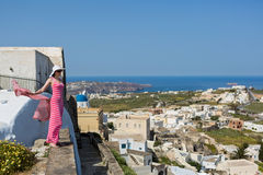 Woman in  long dress, a hat and scarf in his hands. Woman in a long dress, a hat and scarf in his hands, looking at the beauty of island Santorini, Greece Royalty Free Stock Photo